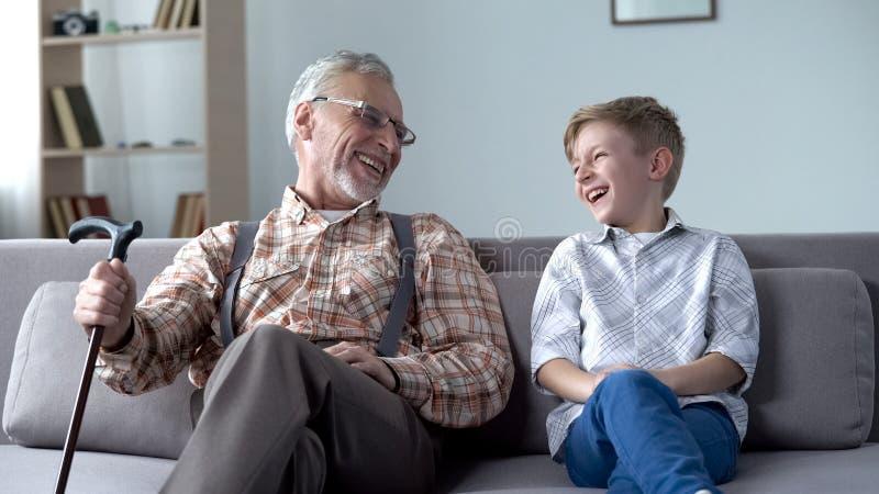 Opa en kleinzoon die, samen gekscherend, waardevolle pretogenblikken echt lachen stock afbeeldingen