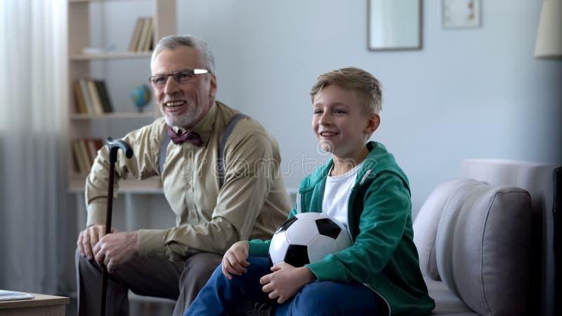 Opa en kleinzoon die voor favoriet voetbalteam toejuichen, gelukkig voor het winnen stock foto
