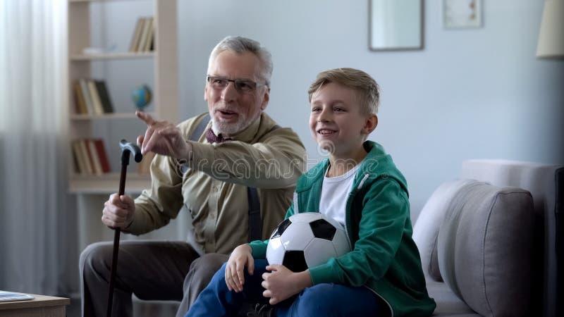 Opa en kleinzoon die voor favoriet voetbalteam toejuichen, gelukkig voor het winnen royalty-vrije stock foto's