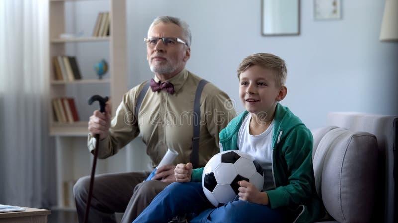 Opa en kleinzoon het letten op voetbal die samen, voor favoriet team toejuichen stock fotografie