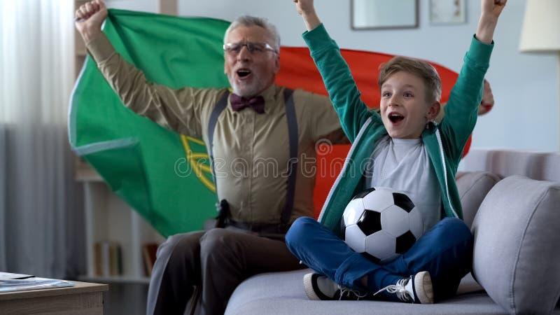 Opa en kleinzoon het letten op voetbal, golvende Portugese vlag, gelukkig voor winst royalty-vrije stock foto's