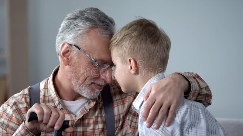 Opa en kleinzoon leunende voorhoofden samen, familieliefde, sentimentaliteit stock afbeelding
