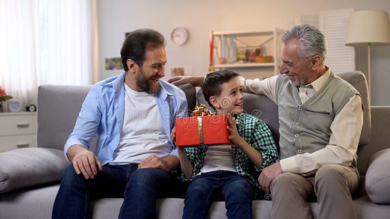 Opa en papa het gelukwensen preteen jongen, die verjaardagsgeschenk in doos geven royalty-vrije stock foto's