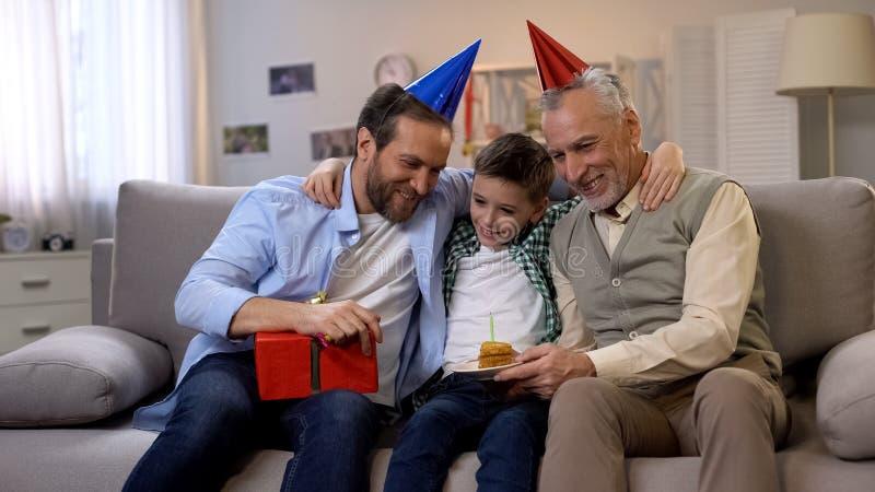 Opa en papa het gelukwensen preteen jongen op B-dag, die giftdoos en cake geven stock afbeeldingen