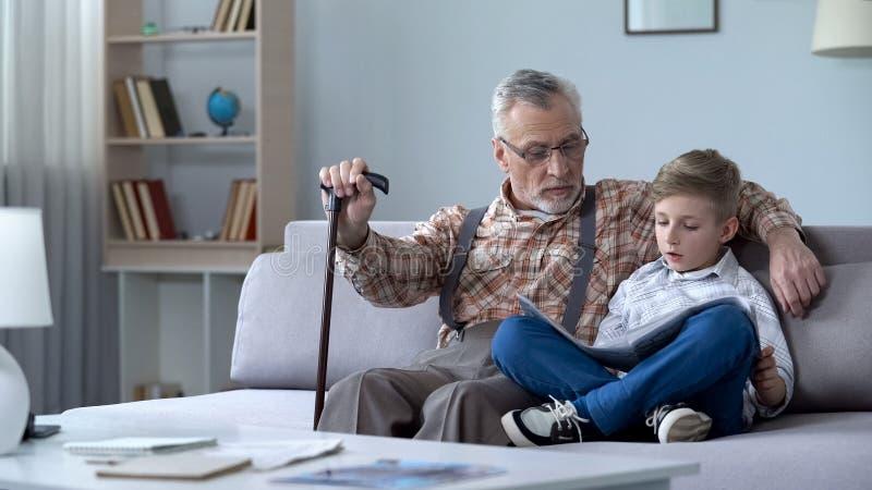 Opa het bekijken kaart met kleinzoon, die reis samen bespreken, lerend aardrijkskunde stock foto's
