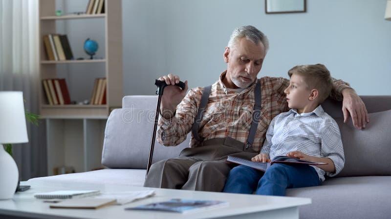 Opa het letten op fotoalbum met kleinzoon, die aan verhalen van de gelukkige jeugd herinneren stock foto's
