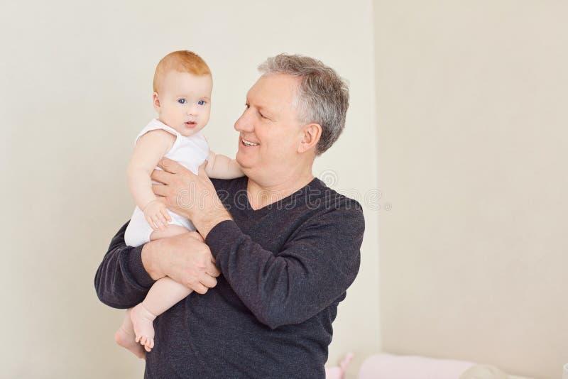 Opa met een babykleindochter in haar wapens royalty-vrije stock foto