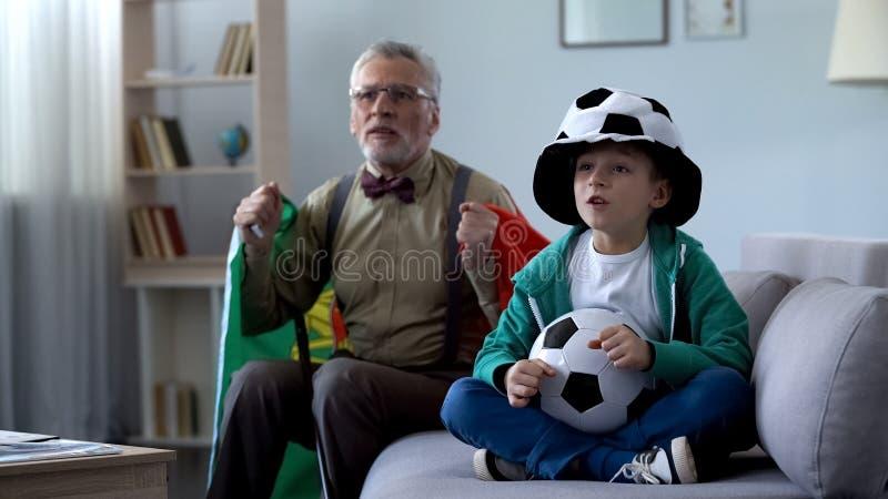 Opa in Portugees vlag het letten op voetbal met jongen wordt verpakt, die zich over spel ongerust maken dat royalty-vrije stock foto