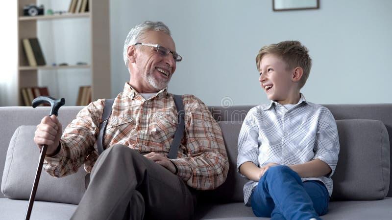 Opa und Enkel, die echt, zusammen scherzend, wertvolle Spaßmomente lacht stockfoto