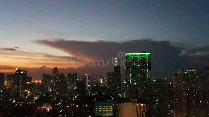 Opacifie le jour de coucher du soleil aux bâtiments de nuit photos stock