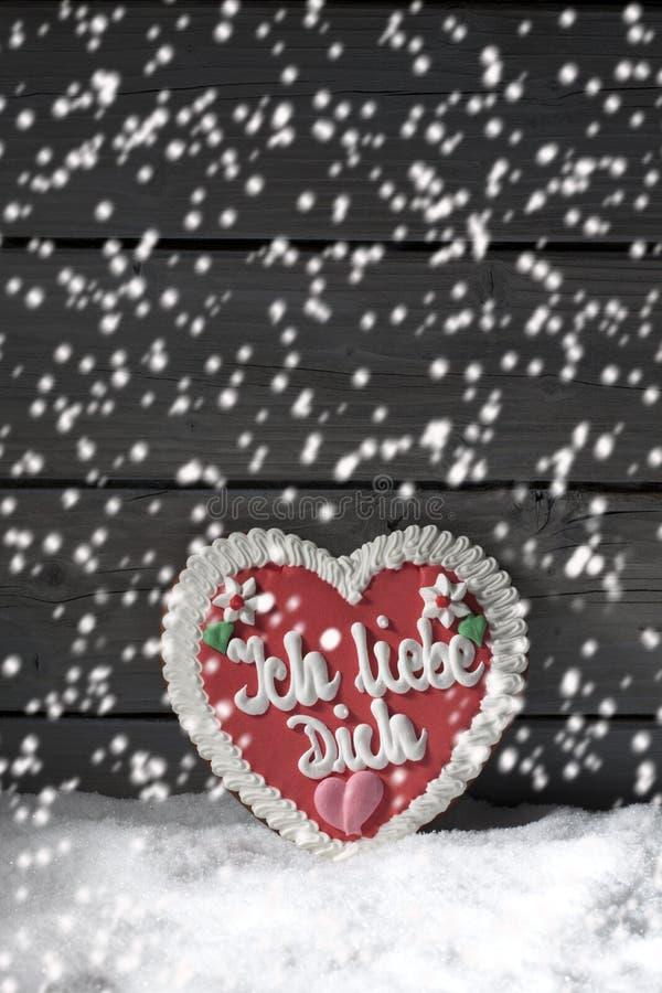 Opad śniegu z piernikowym sercem na rozsypisku śnieg przeciw drewnianemu tłu obraz stock