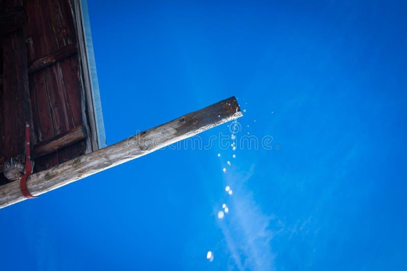 Opadowy spadać od starego drewnianego dachu fotografia stock