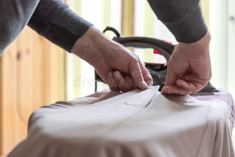 Opahulp het strijken kleding voor oma Nadruk op oude handen royalty-vrije stock afbeeldingen