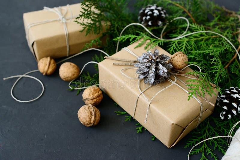 Opakunkowego nieociosanego eco Bożenarodzeniowi prezenty z rzemiosło papieru, smyczkowych i naturalnych jedlinowymi gałąź na ciem obraz royalty free