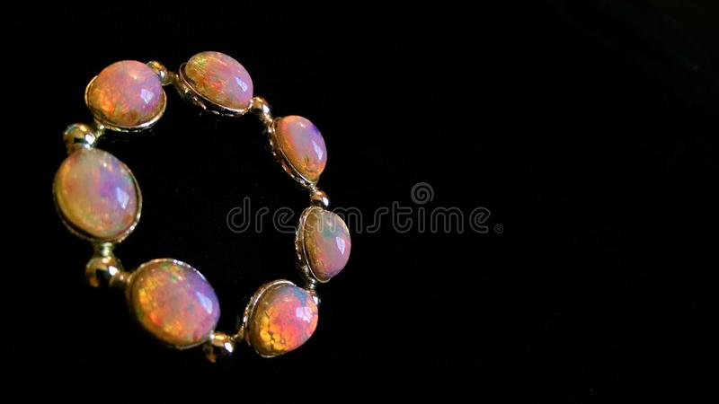 Opal brooch sparkles against black background. An odd number of colorful white opals reflect and refract in the light, in contrast with the stark, dark, abyssal royalty free stock photo