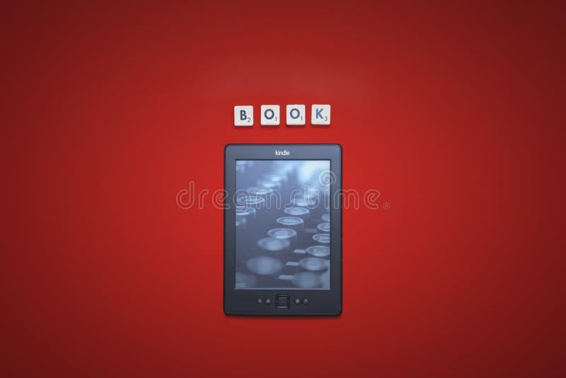 Opalenica, Polônia - 07 23 2016: Leitor eletrônico Amazon Kindle Classic 4 do livro, em um fundo vermelho com a inscrição foto de stock royalty free