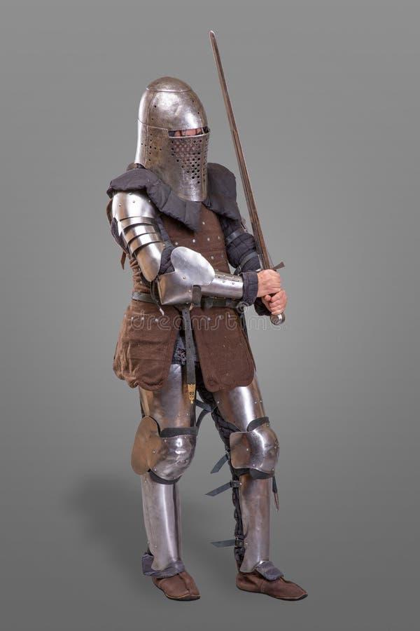 Opancerzony rycerz w hełmie z kordzikiem nad szarym tłem i zdjęcia stock