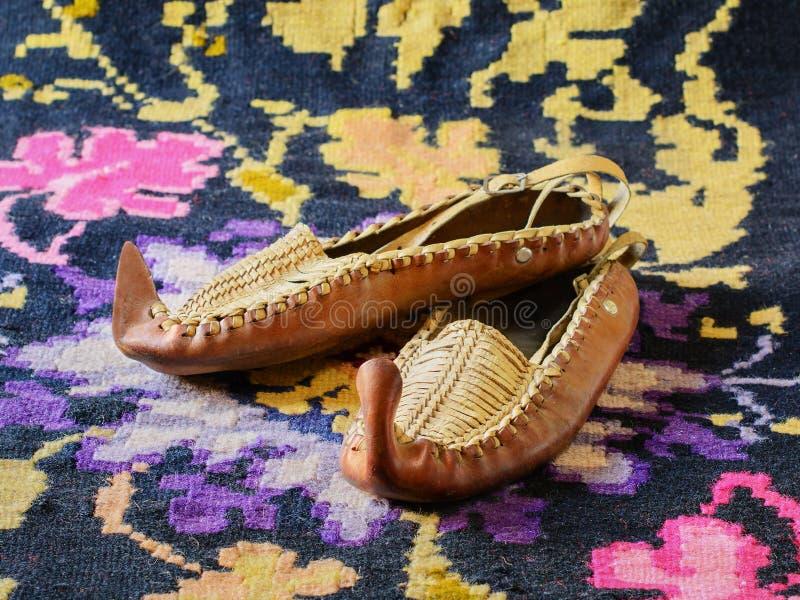 Opanci folk skor för traditionellt serbiskt läder, kilim lägenhet-vävd handgjord filt arkivfoton