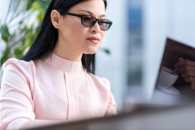 Opanowany żeński działanie laptopem fotografia stock