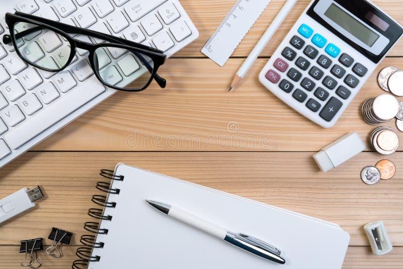 OPansicht des modernen Schreibtischtabellenarbeitsplatzes mit Computertastatur, Gläsern, Taschenrechner, Stift, Bleistift und Mem stockfoto