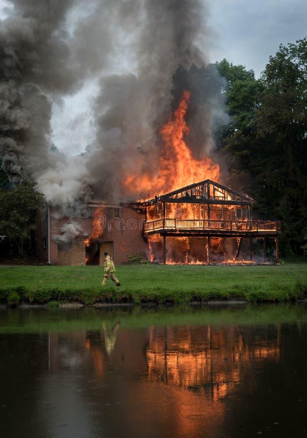 Oparzenie dziecka oparzenie, dom odbija swój płomienie w stawie fotografia stock