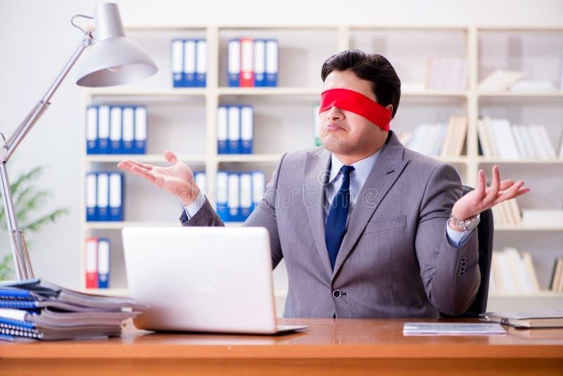 Opaska biznesmena obsiadanie przy biurkiem w biurze zdjęcia stock