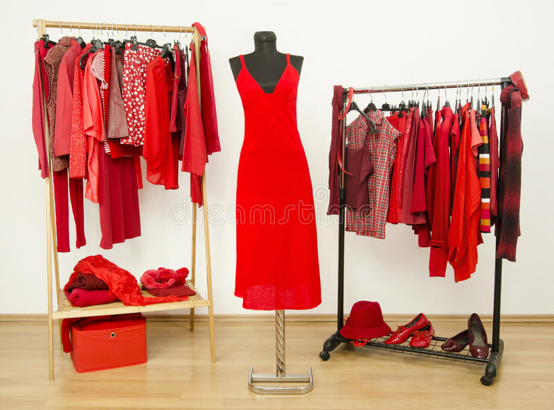 Opatrunkowa szafa z czerwieni ubraniami układał na wieszakach i sukni na mannequin fotografia royalty free