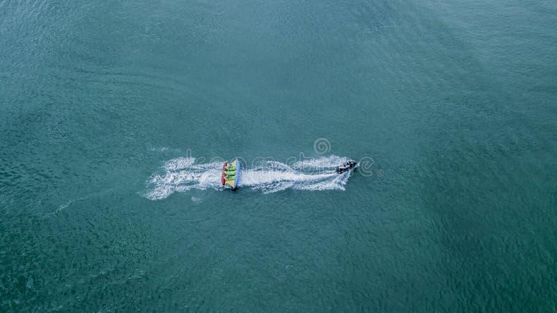 Opblaasbare banaanboot met toeristen in blauwe kalme overzees Groep die mensen banaanboot berijden Weg het verzenden stock afbeelding