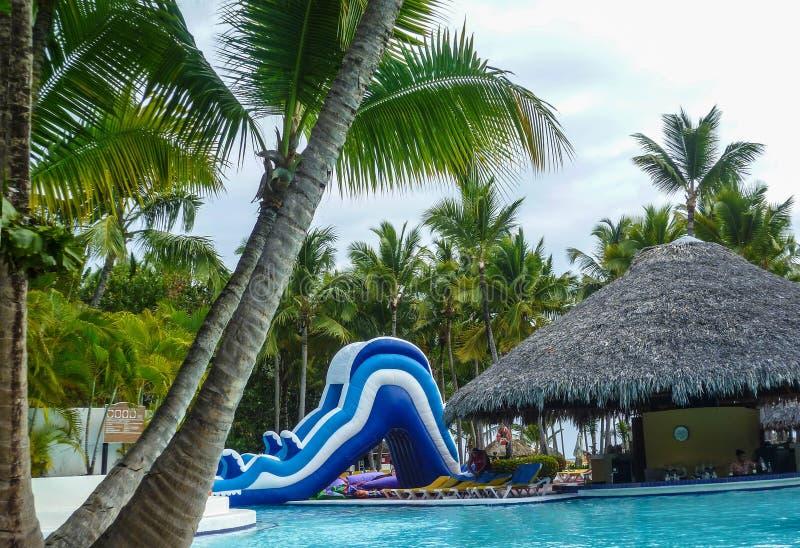 Opblaasbare dia in de buurt van het zwembad en staaf op een zomerdag in de Dominicaanse Republiek stock afbeelding