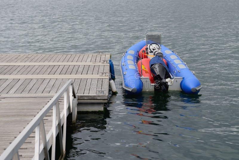 Opblaasbare die motorboot bij houten pijlers wordt vastgelegd royalty-vrije stock foto