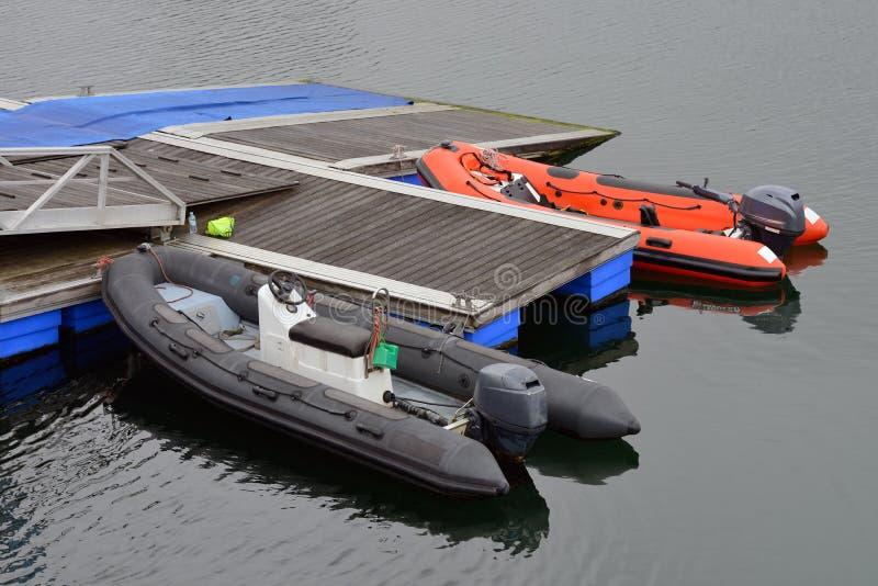 Opblaasbare die motorboot bij houten pijlers wordt vastgelegd stock afbeeldingen