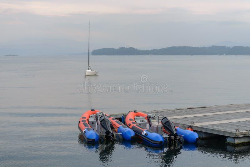 Opblaasbare motorboot bij de houten pijler stock foto's
