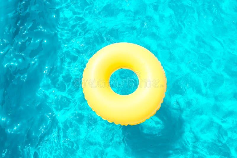 Opblaasbare ring die in de pool op een zonnige dag zwemmen stock afbeelding