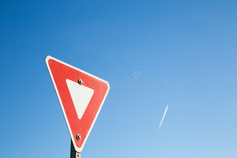 Opbrengstteken tegen een blauwe hemel met een contrail stock foto's