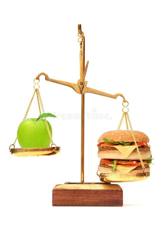 Opción de la dieta entre la manzana y la hamburguesa imágenes de archivo libres de regalías