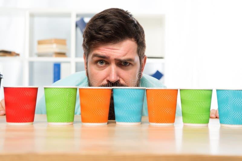 Opción difícil Toma de decisión hombre serio y triste con las tazas de café coloridas Muchas tazas de café opción dura a fotos de archivo