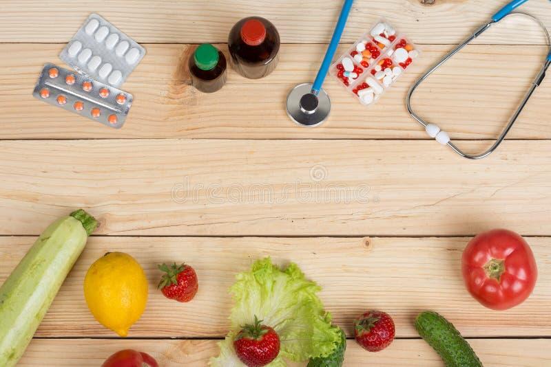 opción entre las vitaminas, verduras, frutas y bayas o tabletas, píldoras y estetoscopio naturales fotografía de archivo libre de regalías