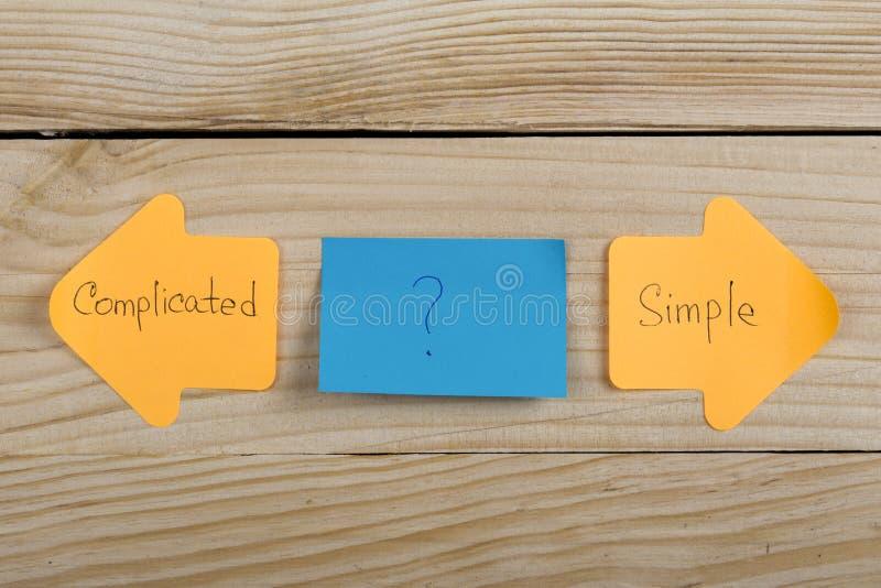 opci?n de la vida - etiquetas engomadas anaranjadas bajo la forma de flechas del ?ndice con el texto complicado y simple en fondo imagenes de archivo