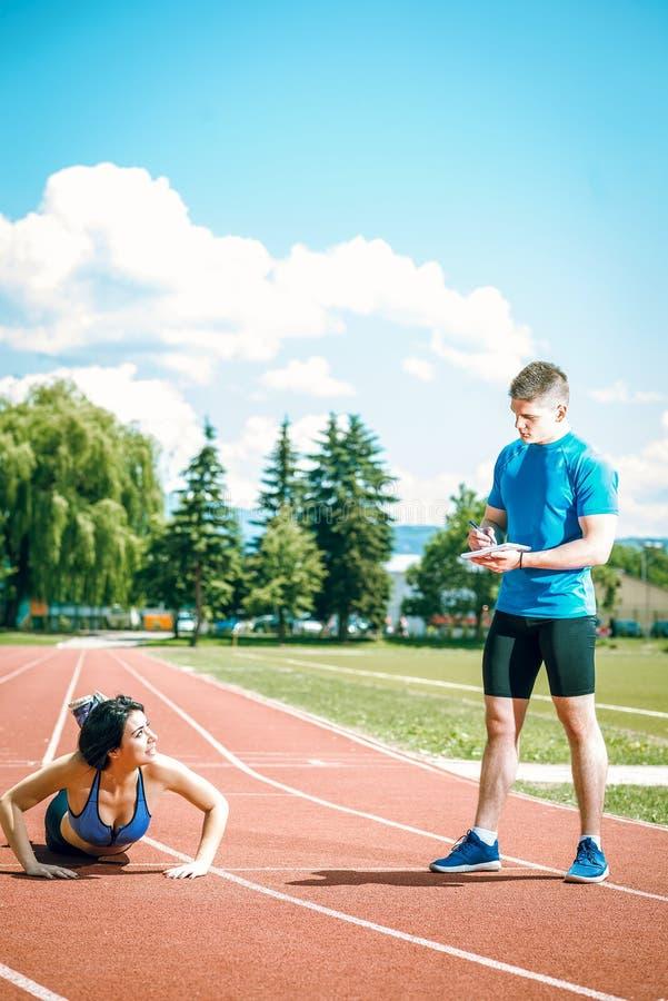 Opdrukoefeningen met trainer openlucht stock fotografie