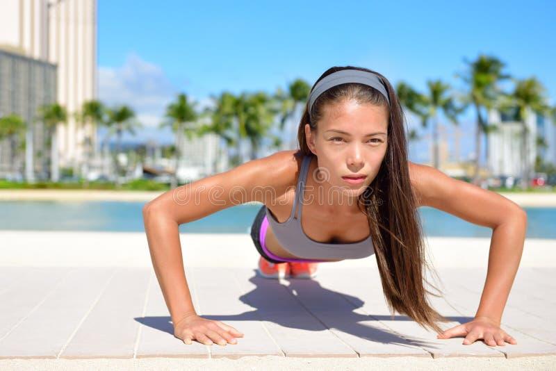 Opdrukoefeningenfitness sportvrouw die opdrukoefeningen buiten doen stock fotografie