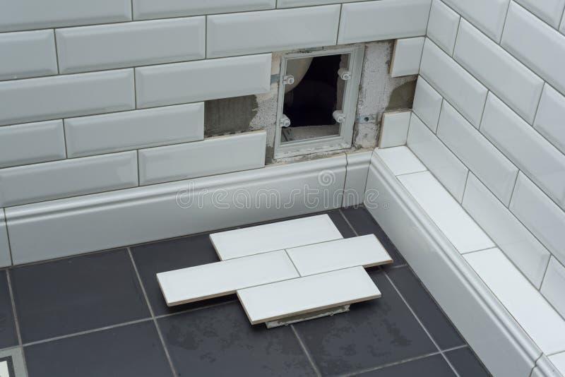 Open在瓦片墙壁上的暗藏的修正有益健康的舱口盖在卫生间下 库存照片