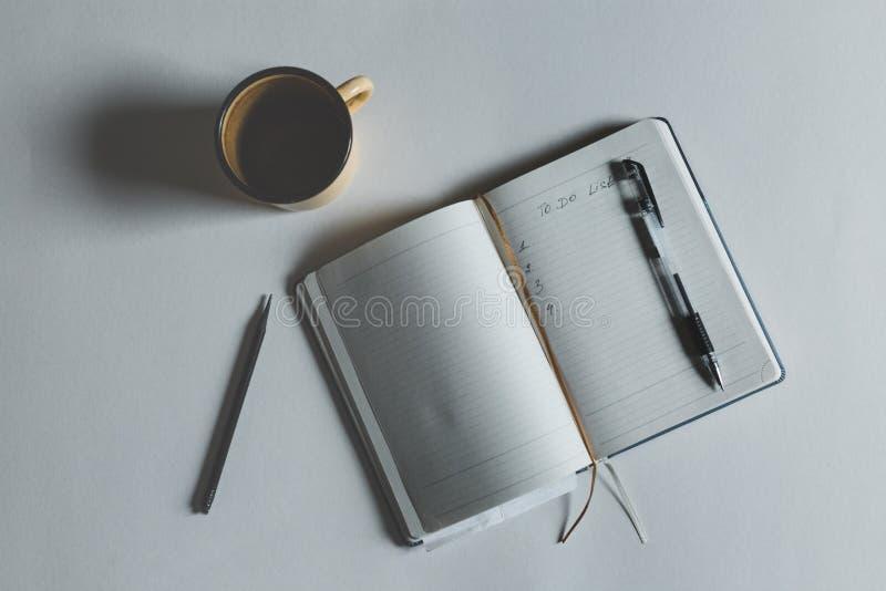 Open笔记本的图象有要做名单的文本的在咖啡在顶视图的旁边 免版税库存图片