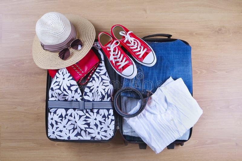 Open упаковал чемодан с женскими одеждами лета и аксессуарами, купальным костюмом, шляпой, солнечными очками, тапками, белой руба стоковая фотография rf