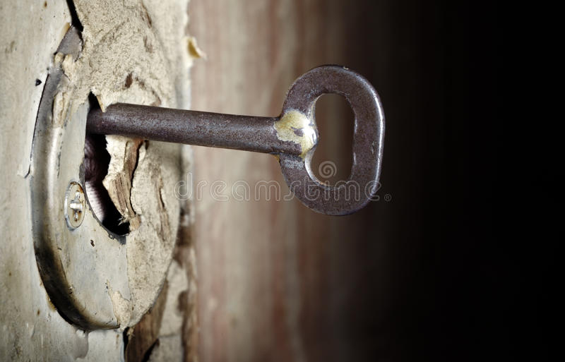 Open. CLose-up photo of the old key inserted into the damaged lock stock photo