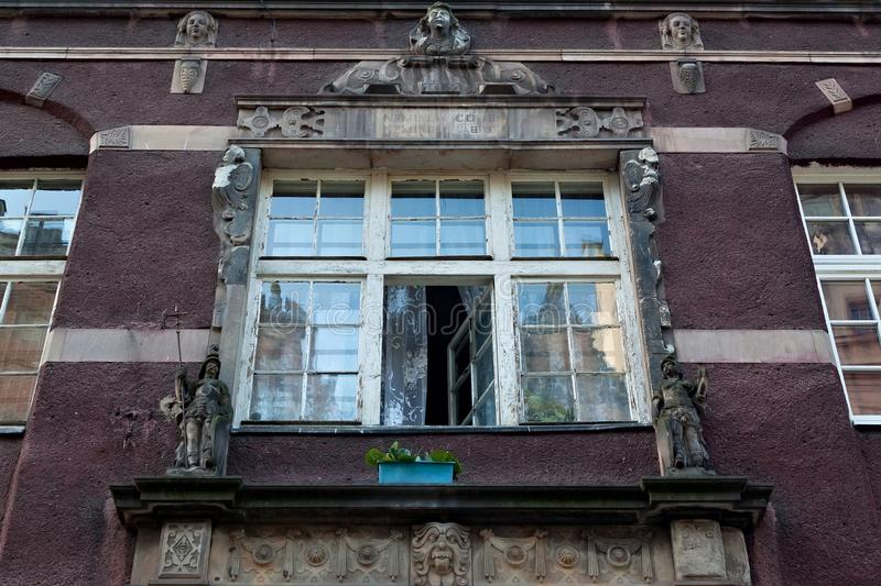 Open aged shabby window with bas-reliefs on one of the historic buildings in the Main Town of Gdansk. stock images