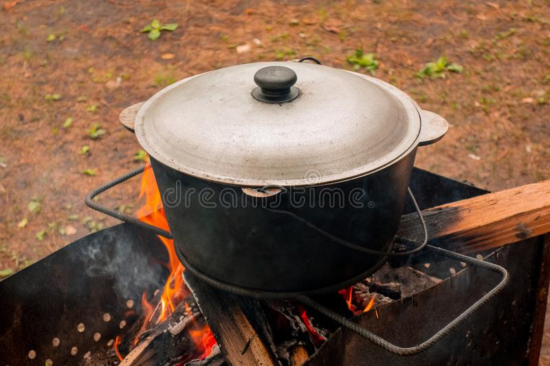 Open air kitchen at party picnic. Pilaf cooking on fire outdoor. Big pot closed with cover stays on wire rack and steams. Close up. Image of meal dish stock image