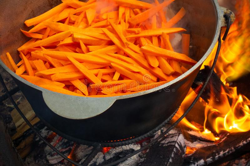 Open air kitchen at party picnic. Pilaf cooking on fire outdoor. Big pot with sliced carrot stays on wire rack and steams. Close. Up image of meal dish stock photography