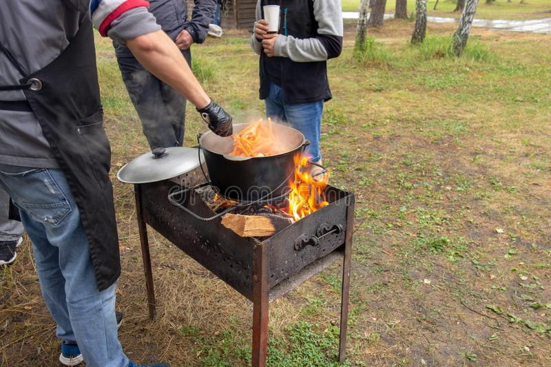 Open air kitchen at party picnic. Pilaf cooking on fire outdoor. Chef cook is stirring meal dish in big pot by ladle. Bushpot. Stays on wire rack and steams royalty free stock image