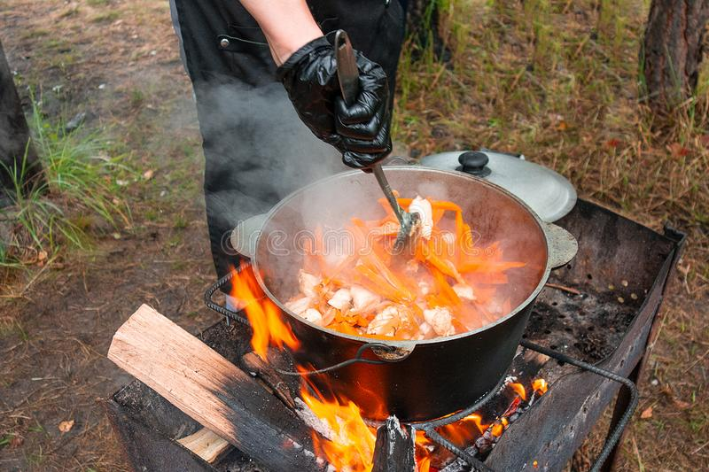 Open air kitchen at party picnic. Pilaf cooking on fire outdoor. Chef cook is stirring meal dish in big pot by ladle. Bushpot. Stays on wire rack and steams royalty free stock photography