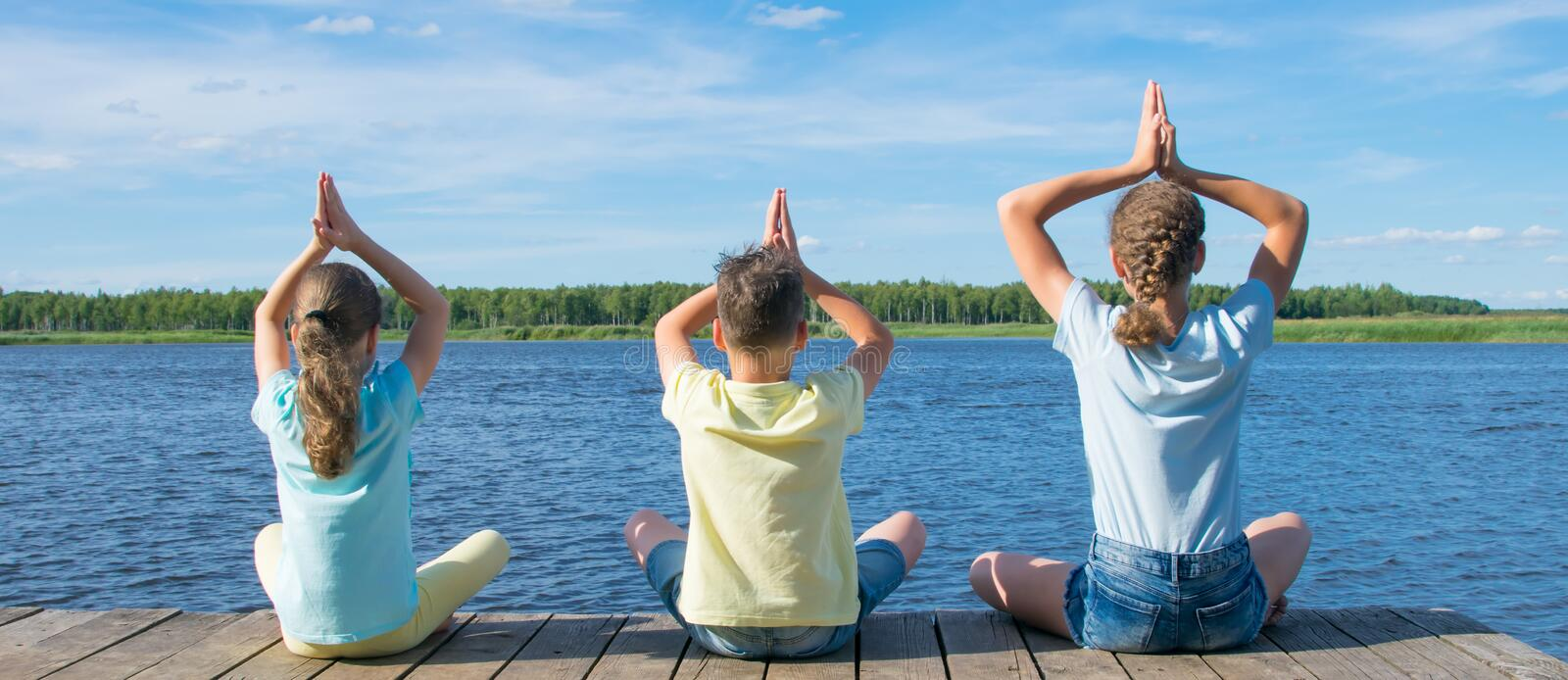 In the open air, on the pier, near the water the company of children is engaged in relaxation in the form of yoga stock photography